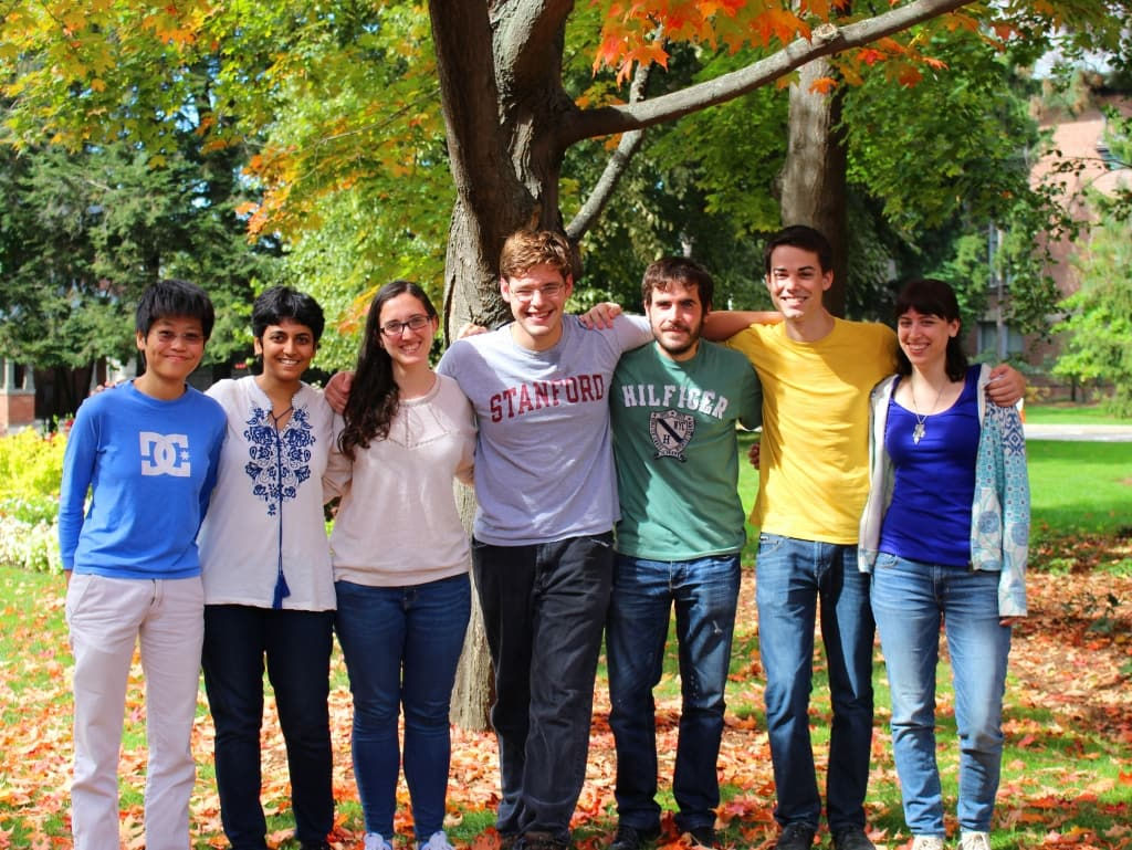 A group of students pose in front of a tree